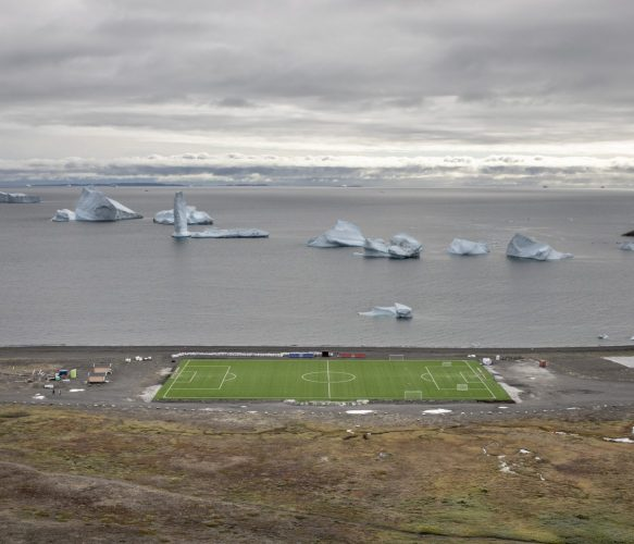 Qeqertarsuaq, Disko Island, Greenland - August 27 2018;The Qeqertarsuaq synthetic stadium with some iceberg on the back. Due to the low temperature, the Greenland Football championship is played in only one week.Qeqertarsuaq is a port and town in Qeqertalik municipality, located on the south coast of Disko Island on the west coast of Greenland. Founded in 1773, the town is now home to a campus of the University of Copenhagen known as Arctic Station.