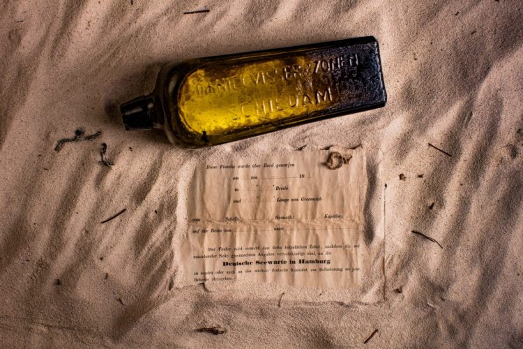 """This undated photo received courtesy from Kym Illman on March 7, 2018 shows a bottle and the  almost 132-year-old message it contained, that was found near Wedge Island, some 160 kilometres (99 miles) north of Perth. The world's oldest known message in a bottle has been found half-buried in sand dunes on Australia's west coast by a group of beach walkers. The oblong object was discovered near Wedge Island, some 160 kilometres (99 miles) north of Perth, in January.  / AFP PHOTO / KYM ILLMAN / - / RESTRICTED TO EDITORIAL USE - MANDATORY CREDIT """"AFP PHOTO /COURTESY OF KYM ILLMAN """" - NO MARKETING - NO ADVERTISING CAMPAIGNS - DISTRIBUTED AS A SERVICE TO CLIENTS"""